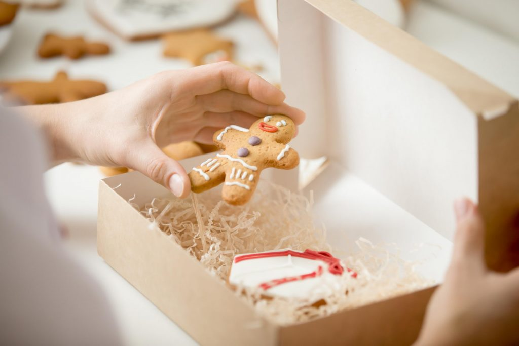 close up confectioner hand packing gingerman into box